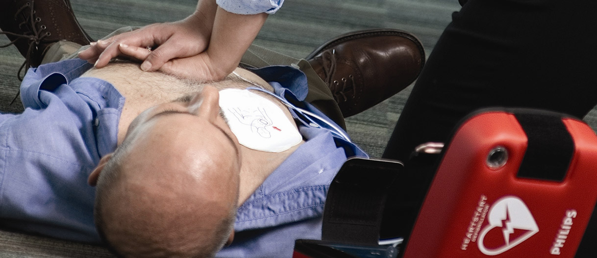 Doing CPR on a patient with an AED