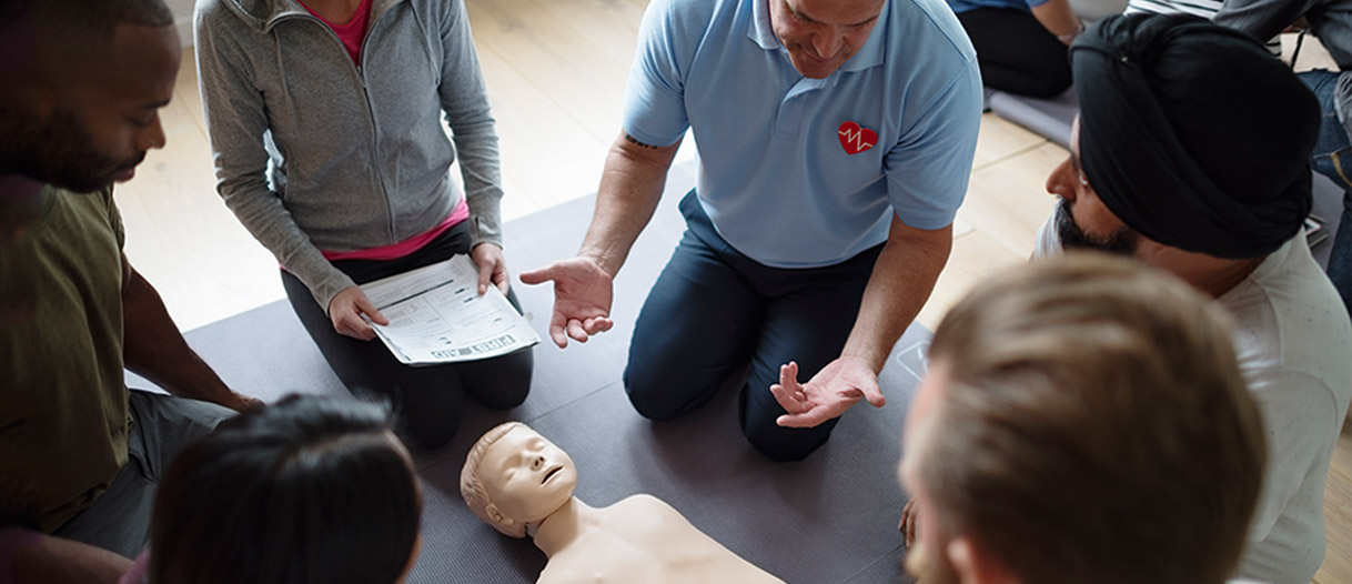 Adults being trained first aid on a child manikin